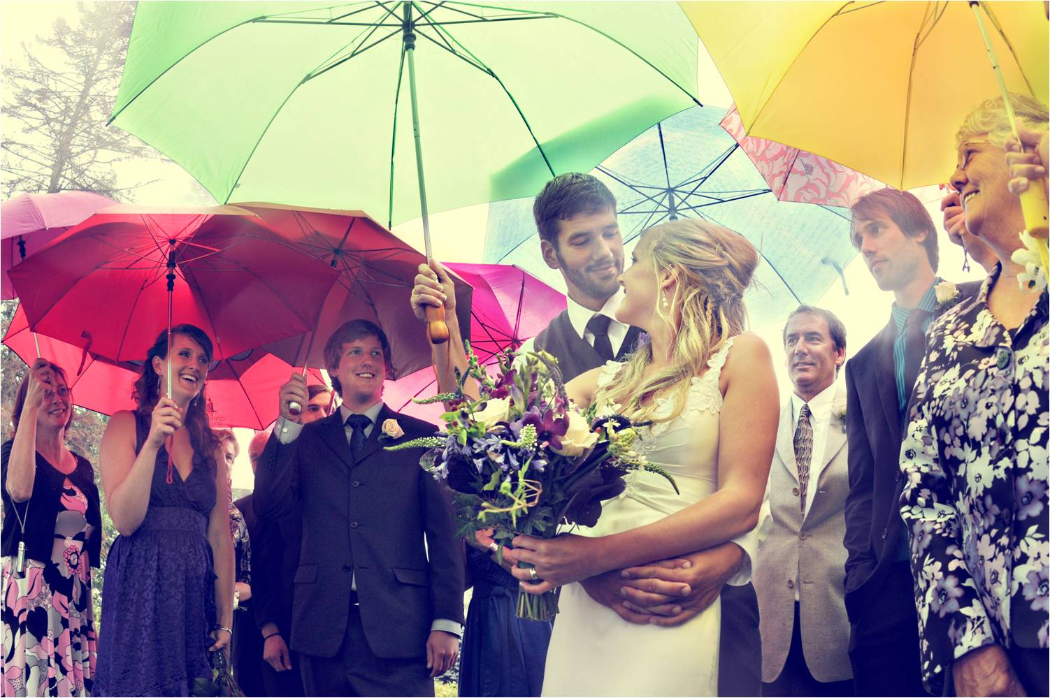 Bride-and-groom-pose-under-vibrant-umbrellas-with-wedding-guests.original