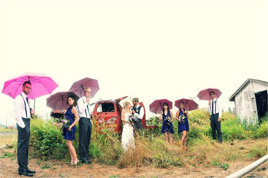 Bride, groom and wedding party pose outside with colorful umbrellas