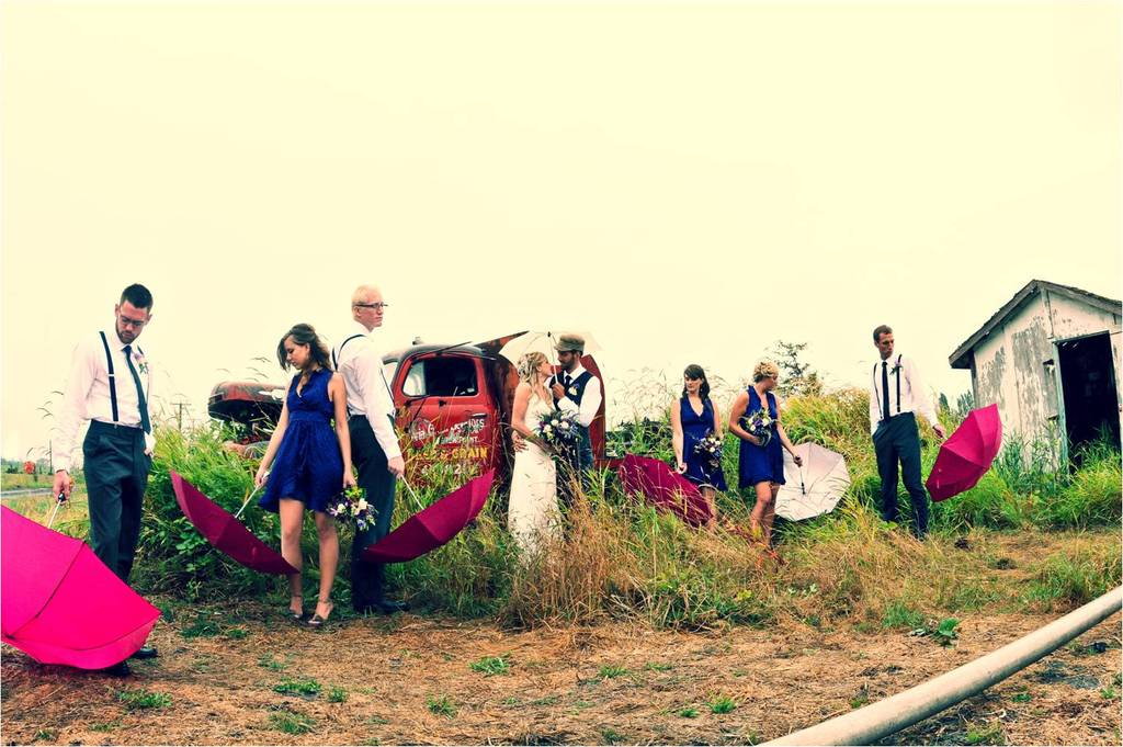 Bride and groom pose outside with wedding party, hold colorful umbrellas