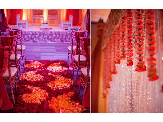 Wedding ceremony aisle covered in rich red rose petals