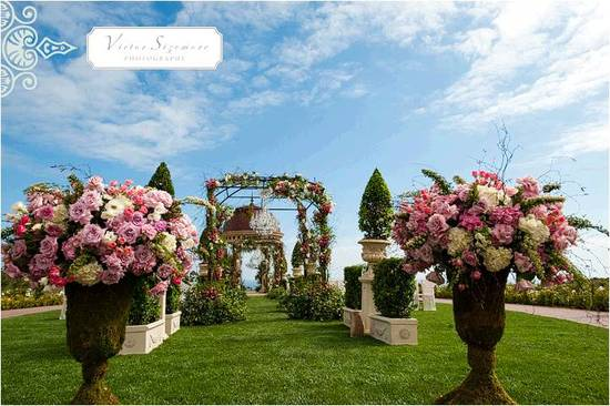 Stunning outdoor wedding venue in California with romantic floral topiaries lining the white aisle