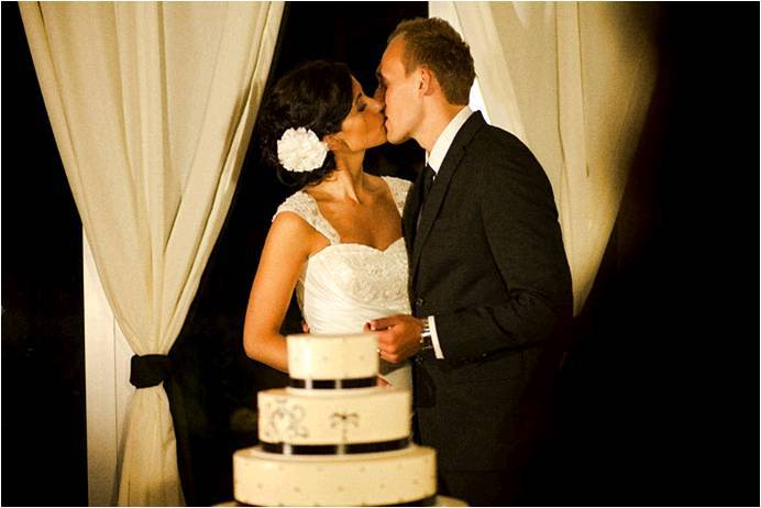 Bride-and-groom-kiss-white-wedding-cake-black-scroll-pattern.full