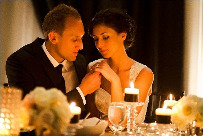 Bride-and-groom-sit-at-sweetheart-table-wedding-reception-candlelight.full