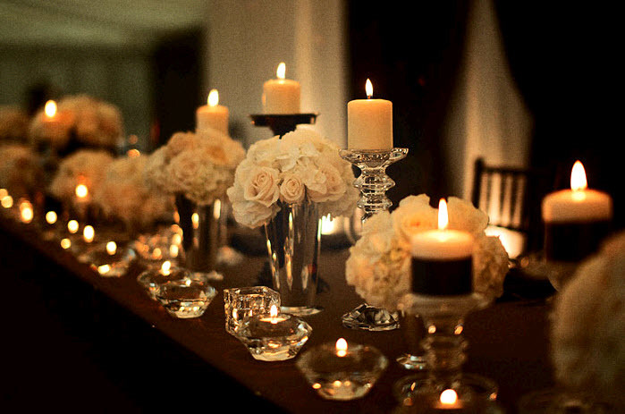 Elegant wedding reception tablescape with white flowers and lots of candlelight