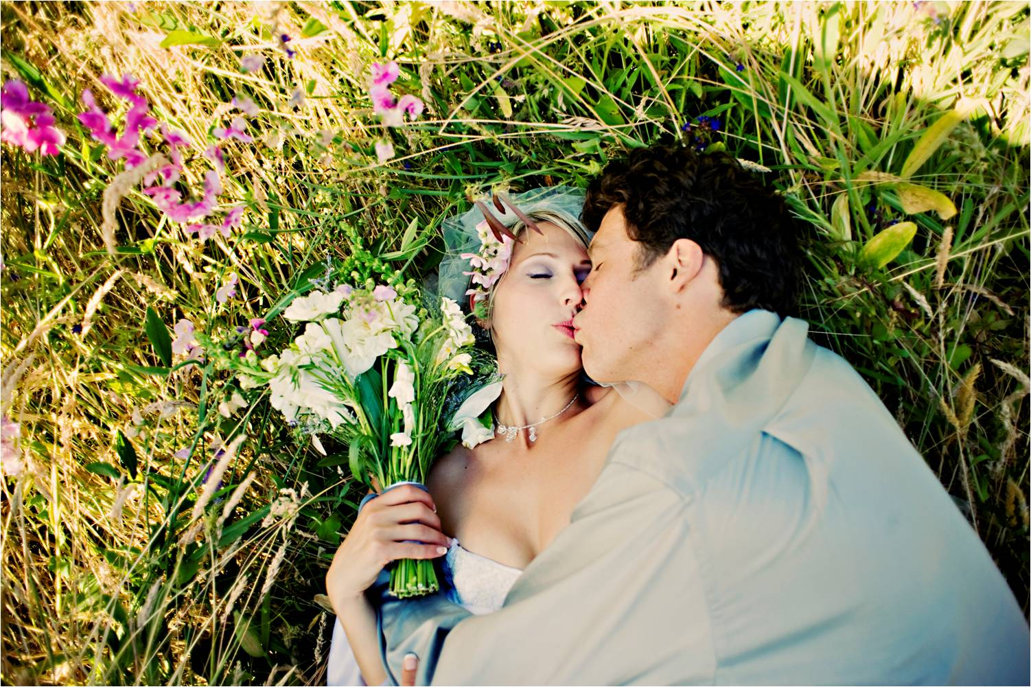 Bride and groom lay in grass in full wedding attire after