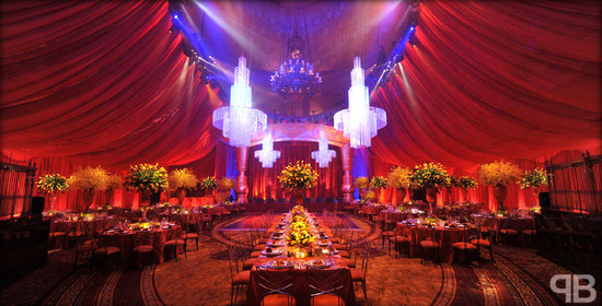 Stunning wedding reception decor with draped fabric from ceiling, sparking chandeliers, and unique r