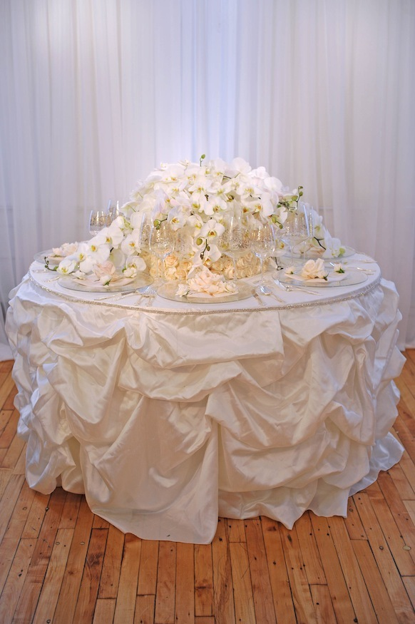 White textured wedding tablescape with orchid centerpiece and lots of candles