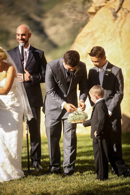 Groom accepts ring from ring bearer