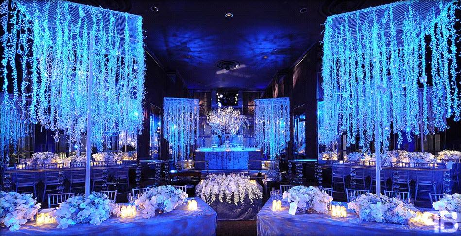 Winter wonderland wedding with blue lighting and hanging crystals | OneWed.com