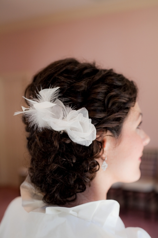 Brunette bride wears low bridal updo with white flower hair accessory