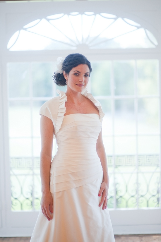 Brunette bride with thick curly hair wears romantic bridal updo and ivory strapless wedding dress