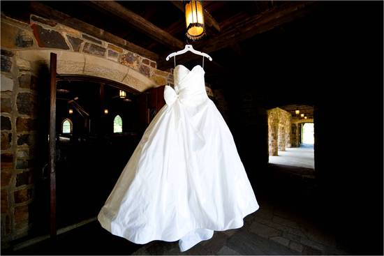 White Priscilla of Boston ballgown wedding dress hangs in venue