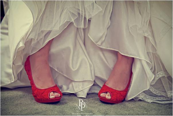 Bride wears ivory wedding dress and red peep-toe bridal heels
