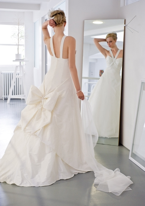 Ivory full a-line wedding dress with halter neckline and large bow on train