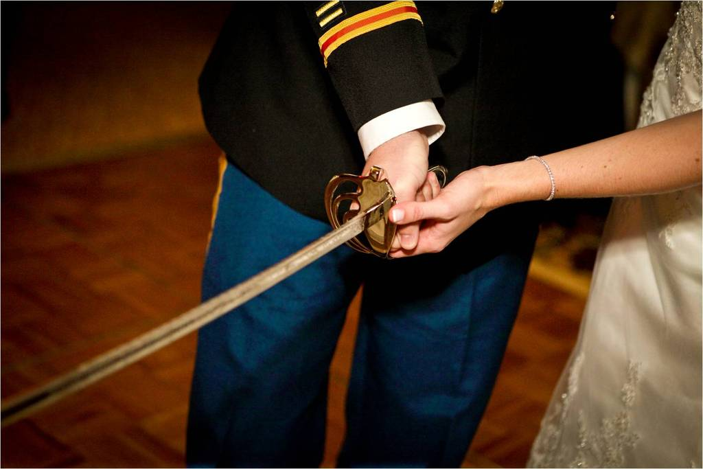 Bride-groom-cut-classic-white-wedding-cake-with-military-sword.full