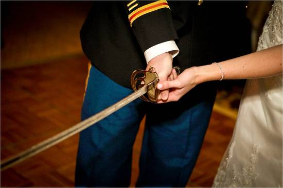 Bride and military groom cut wedding cake with large military sword