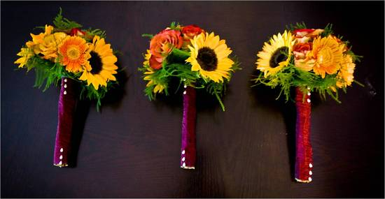 Rich fall wedding bridesmaids' bouquets with sunflowers and roses, wrapped with satin ribbon