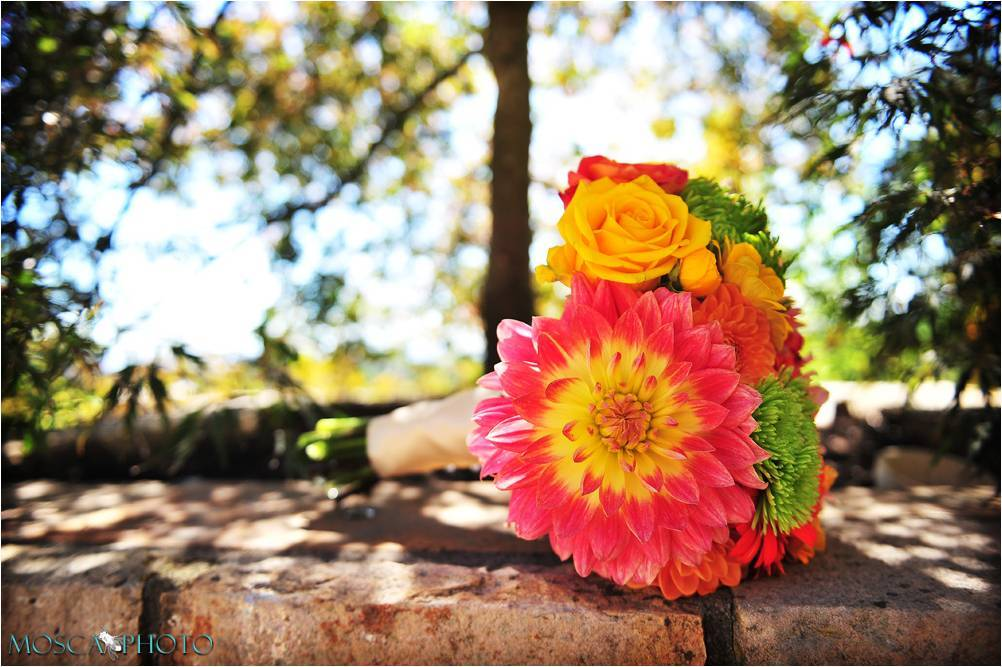 Bright bridal bouquet made with yellow and pink roses, and bright Gerbera daisies