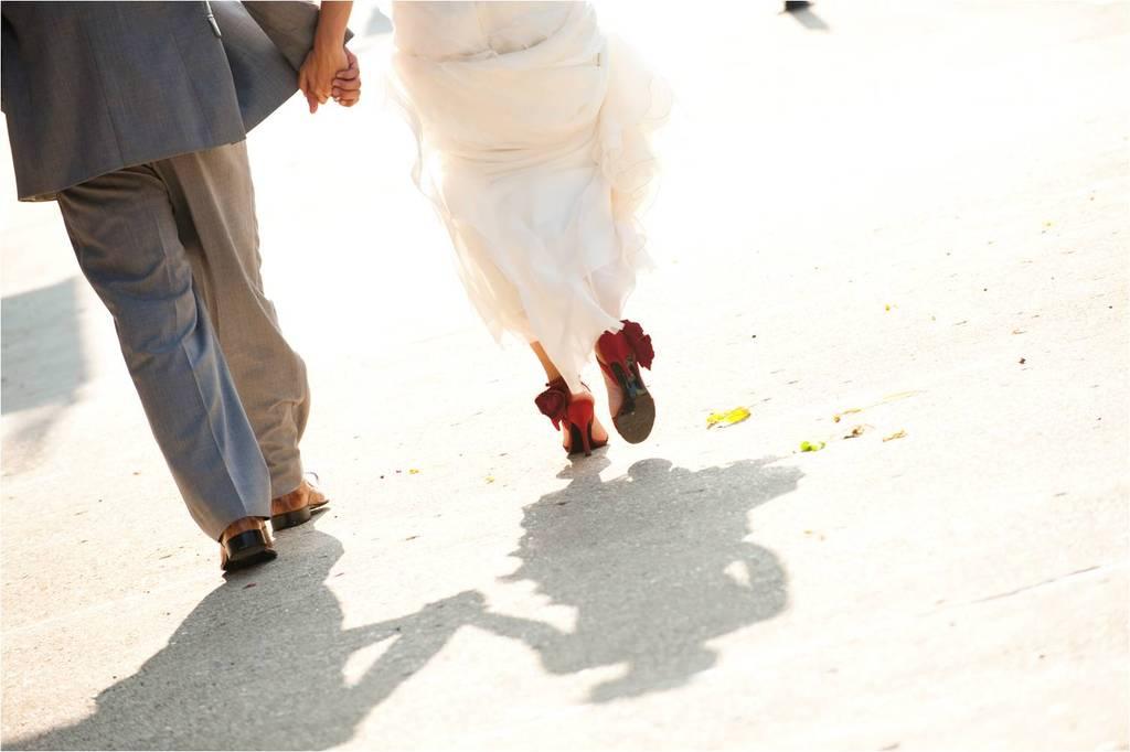 Groom-in-grey-casual-suit-bride-in-white-wedding-dress-red-bridal-heels-walk-hand-in-hand.full