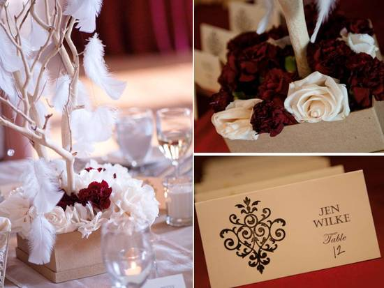 Deep red and ivory wedding reception decor with roses, manzanita branches and feathers