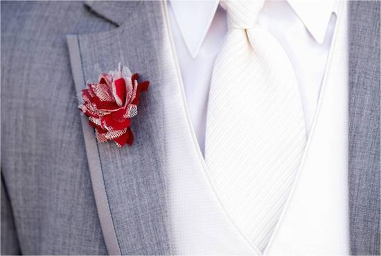Groom wearing grey suit, white shirt and tie, and red and white boutonniere made by his bride