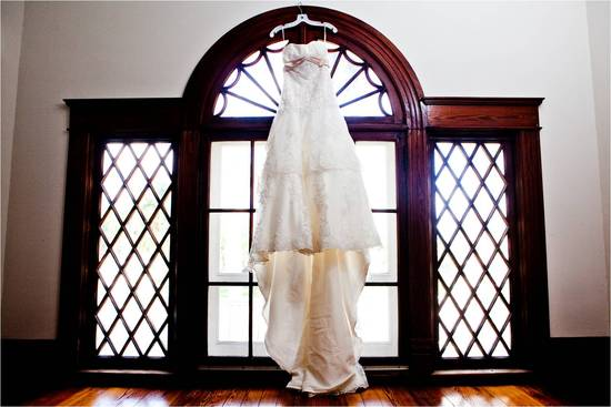 Classic ivory lace wedding dress hangs in gorgeous Florida window