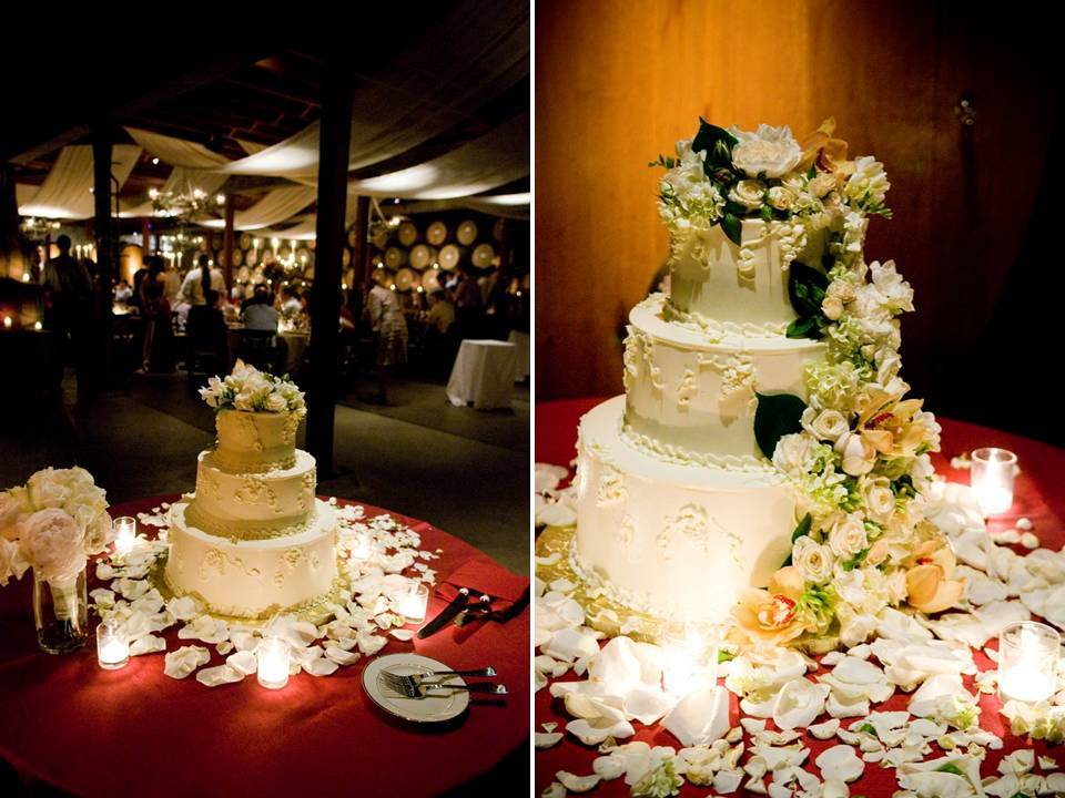 Classic white three-tier wedding cake adorned with white and ivory flowers