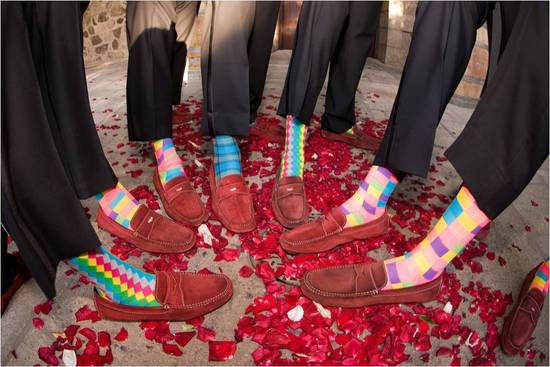 Groom and groomsmen show off red suede shoes and funky colorful socks