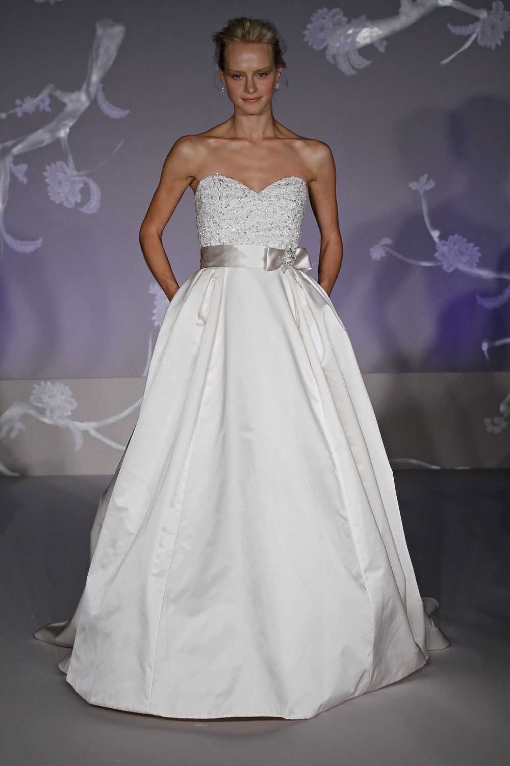Classic ivory ballgown wedding dress with sweetheart neckline, pockets, and sash