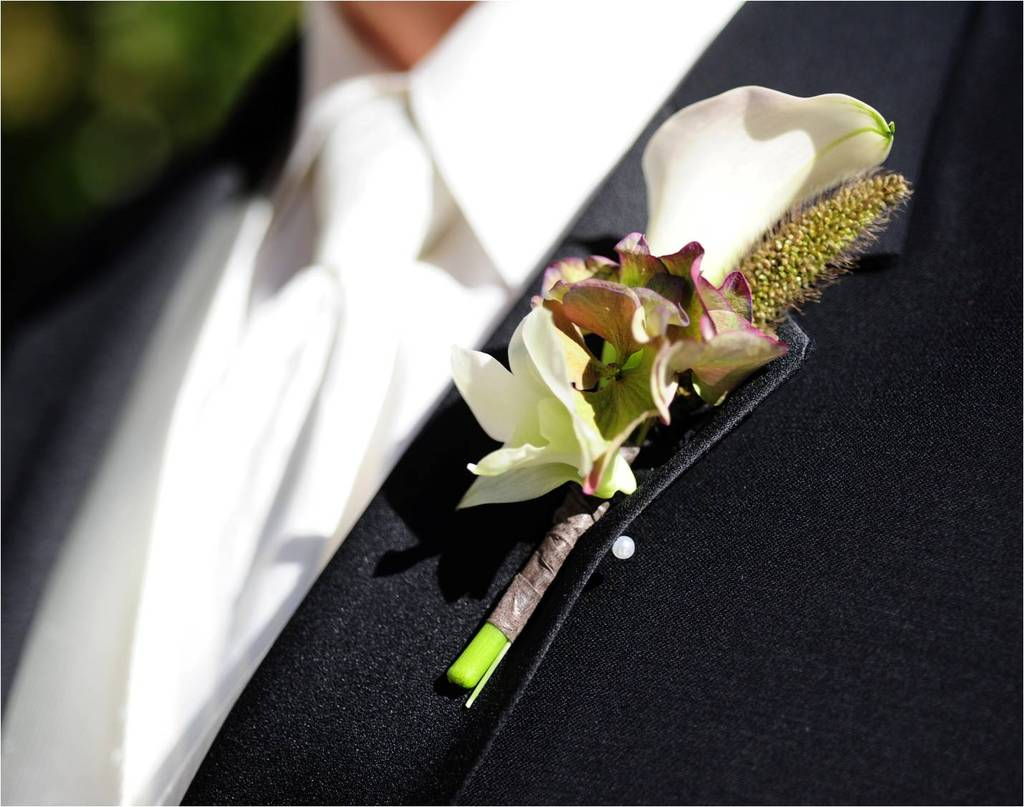 Groom wears traditional black tux and white shirt & tie, unique boutinierre