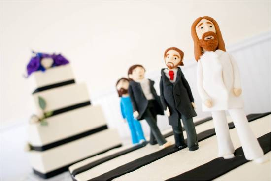 Fun wedding cake toppers adorn classic wedding cake