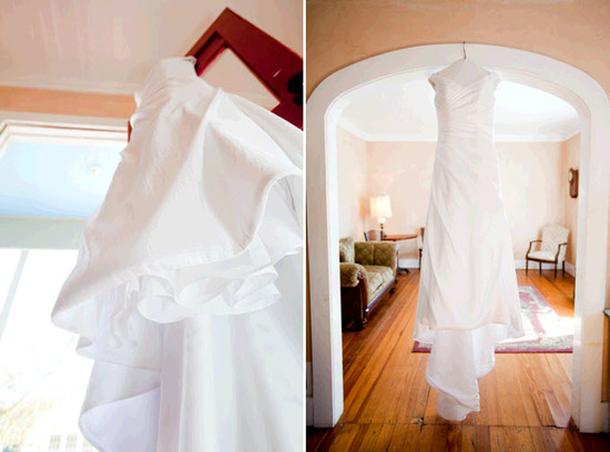 Bride's white classic off-the-shoulder-wedding dress hangs in doorway