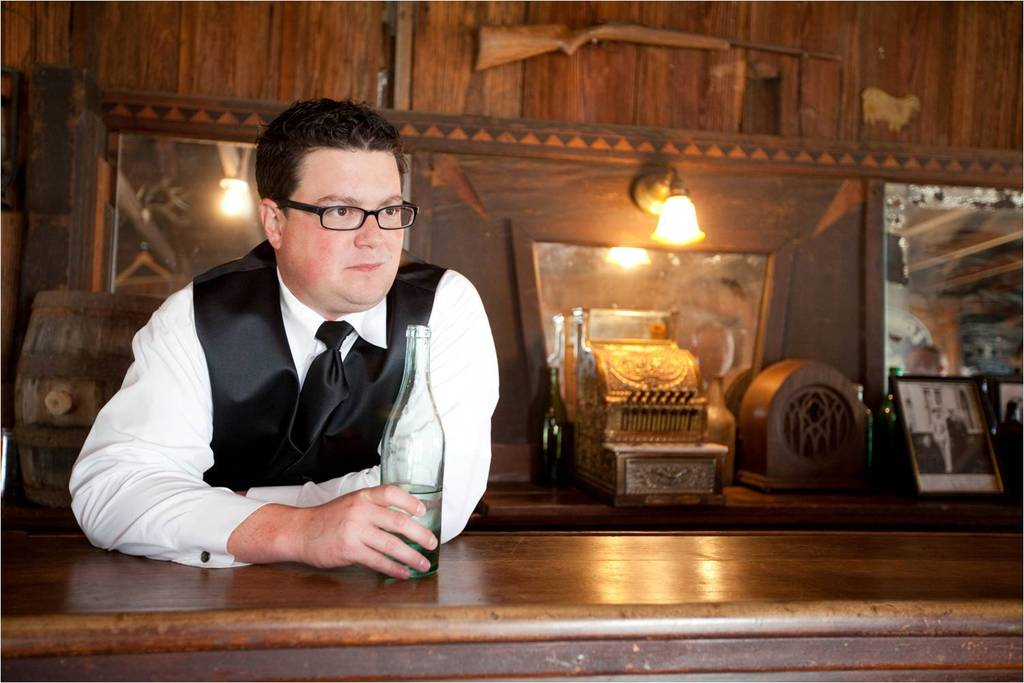 Austin, Texas best man has a drink in old western saloon before the wedding