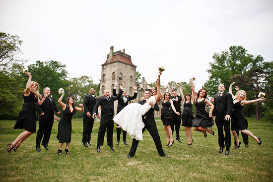 Groom lifts blushing bride, entire wedding party jumps behind with castle venue as backdrop