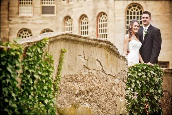 Bride and groom pose in front of Castle venue in Pennsylvania