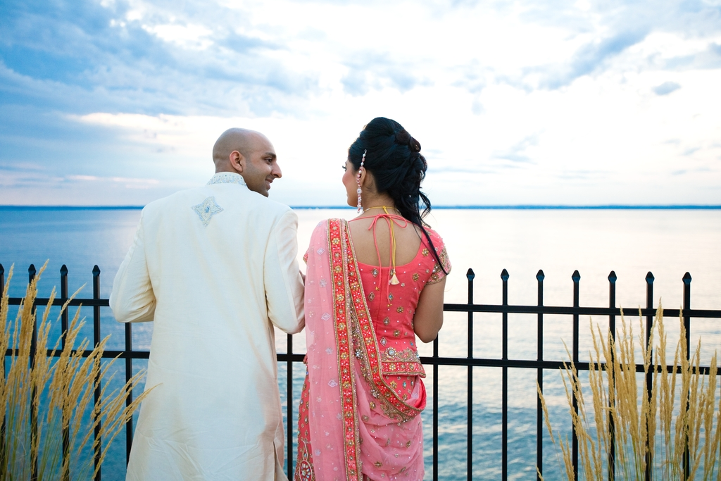 Bride-and-groom-stand-outside-waterfront-new-york-reception-venue-pink-red-gold-sari.full