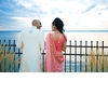 Bride-and-groom-stand-outside-waterfront-new-york-reception-venue-pink-red-gold-sari.square