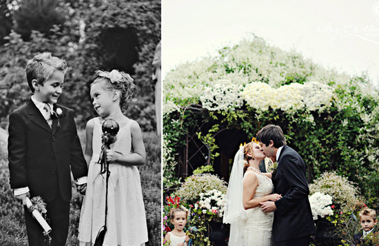 Adorable flower girl and ring bearer hold hands, look on as bride and groom say I Do