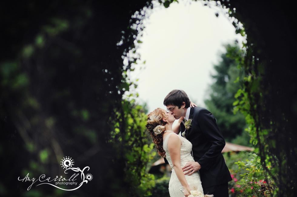 Bride-groom-vintage-wedding-kiss-outside-amidst-garden-of-wedding-venue.full