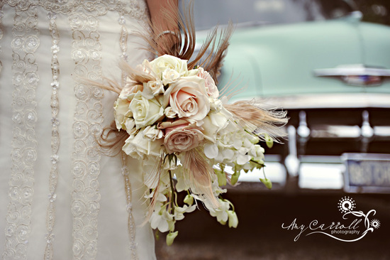 Vintage bride holds unique bridal bouquet of ivory and dusty pink roses, vintage feathers