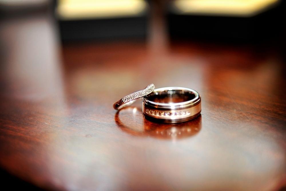 Artistic-wedding-photography-engagement-ring-wedding-bands-pave-diamonds-photographed-on-dark-mahagony.full