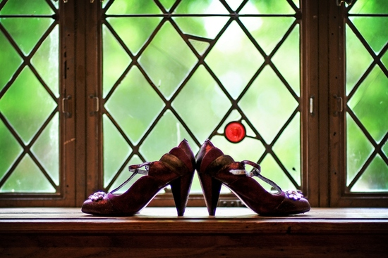 Bride's eggplant purple bridal heels photographed in castle window