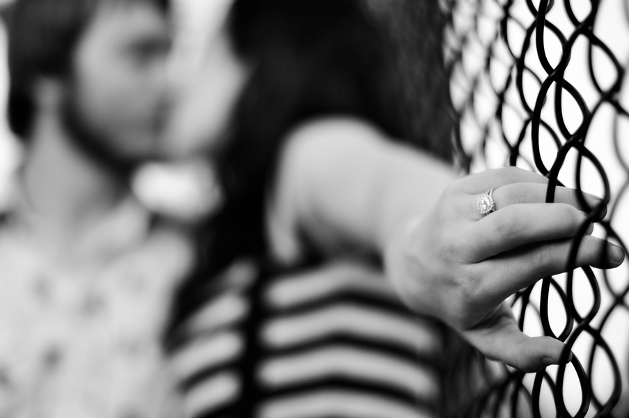 Bride-wears-cushion-cut-diamond-engagement-ring-holds-onto-fence-groom-kisses-her-passionately.full