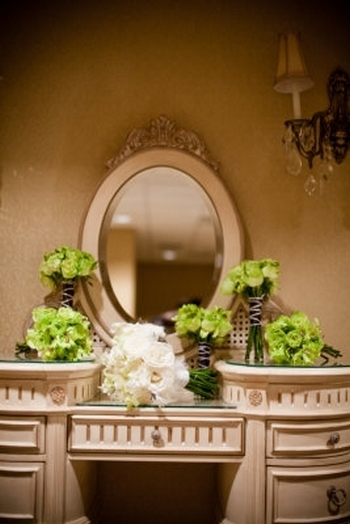 Vintage boudoir inspired vanity at wedding reception venue with ivory rose bridal bouquet