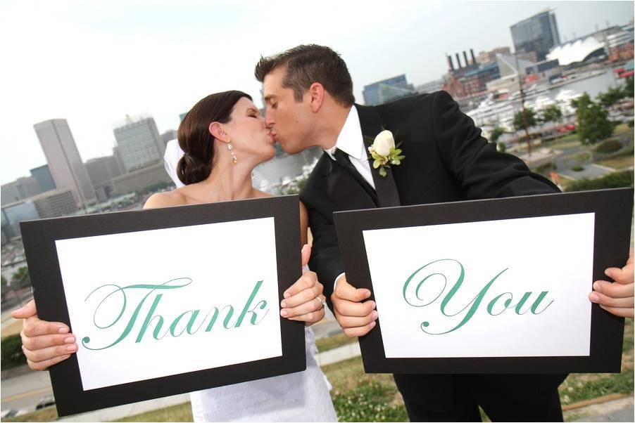 Bride-groom-kiss-after-saying-i-do-hold-thank-you-signs.full