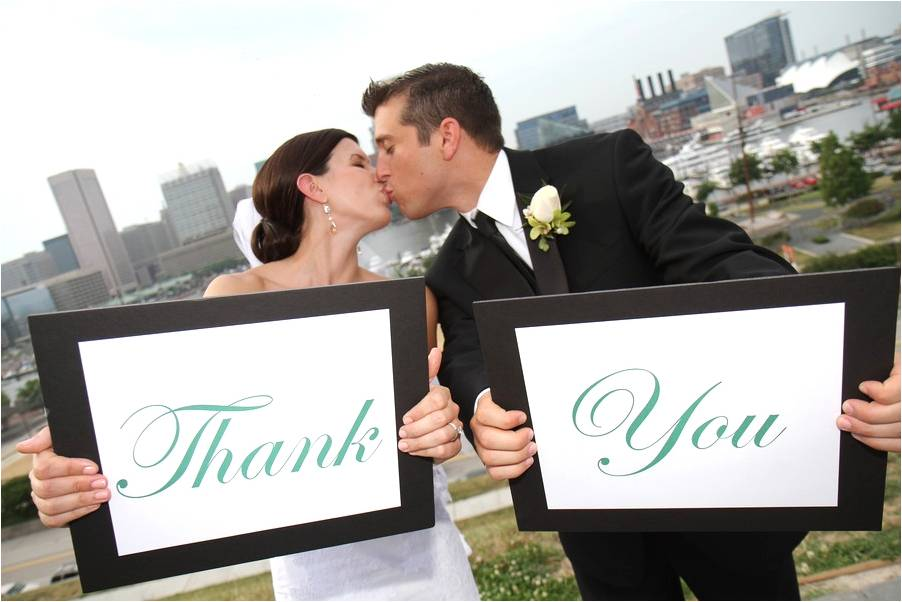 Bride-groom-kiss-after-saying-i-do-hold-thank-you-signs.original