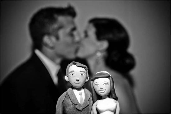 Life-like bride and groom wedding cake topper, real bride and groom kiss in back
