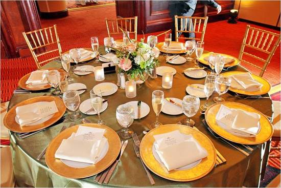 Opulent wedding reception table decor- gold charger plates and tablecloth, simple floral centerpiece