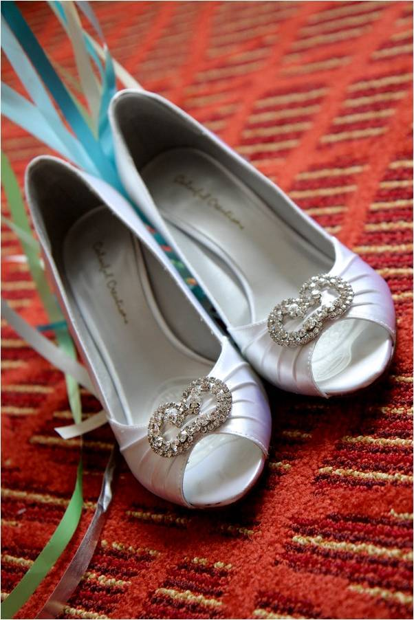 White satin peep-toe bridal heels with rhinestone brooch in center