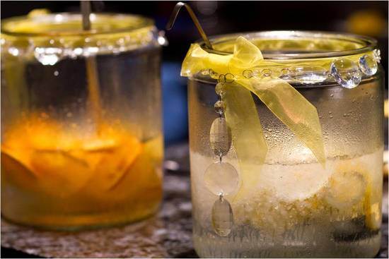Signature cocktails at wedding reception decorated with yellow ribbon and hanging crystals